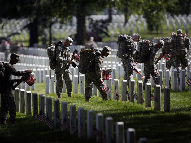 Members of the U.S. Army Old Guard place a flag at each of the over 220,000 graves of fallen U.S. military service members buried at Arlington National Cemetery, May 24, 2012. Memorial Day will be commemorated this weekend across the United States.    REUTERS/Jason Reed  (UNITED STATES - Tags: MILITARY) - RTR32L4M